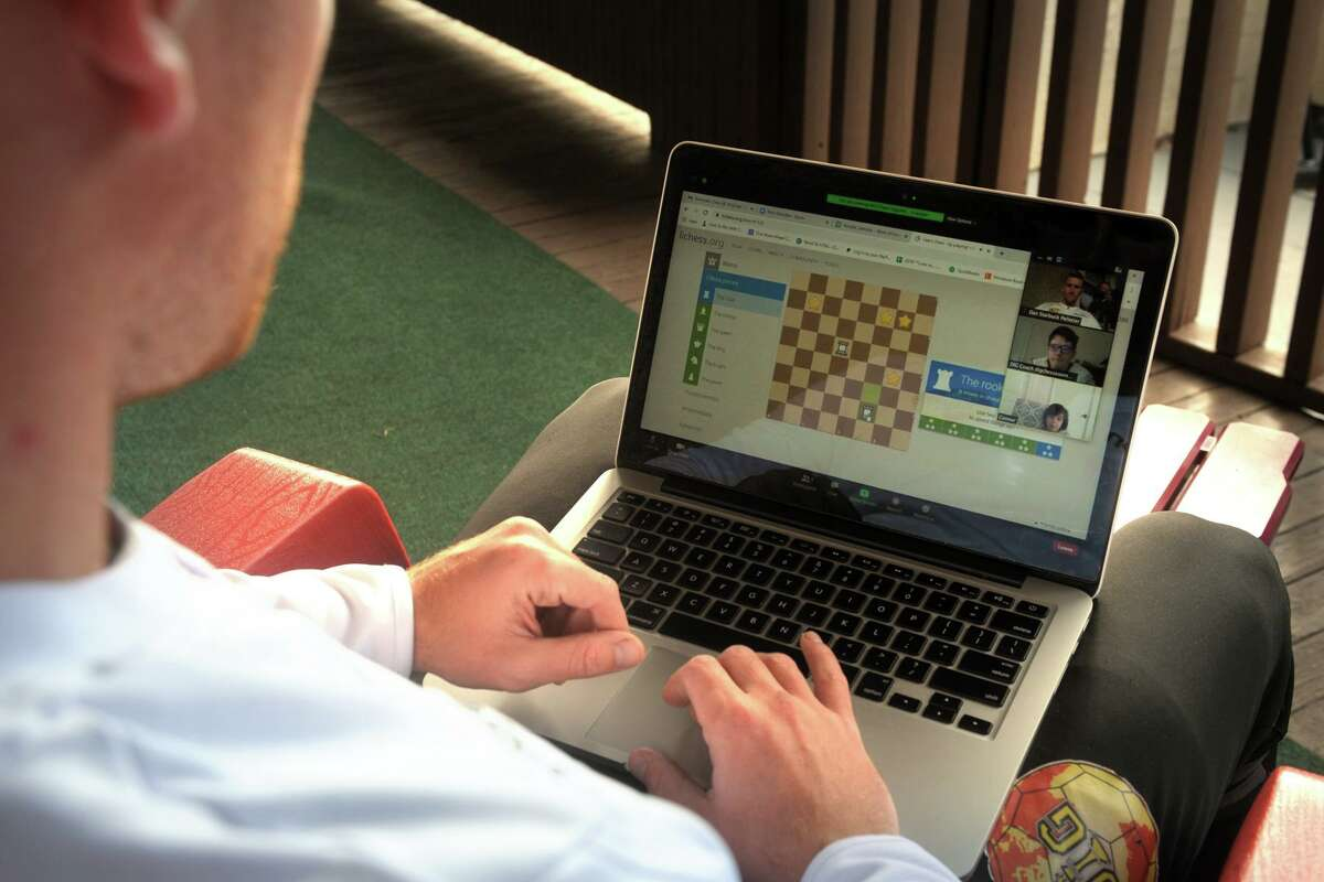 Dan Pelletier, founder and president of DIG USA, watches on his laptop as students play an online game of chess, seen here at his home in Shelton, Conn. Nov. 25, 2020.