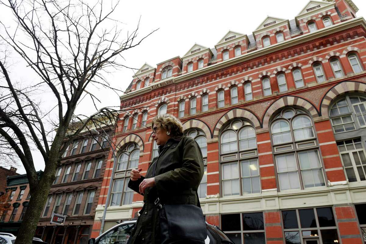 Diana S. Waite stands across from the Rice Building on Friday, Nov. 13, 2020,13, 2020, on 2nd Street in Troy, N.Y. It is featured in her book,