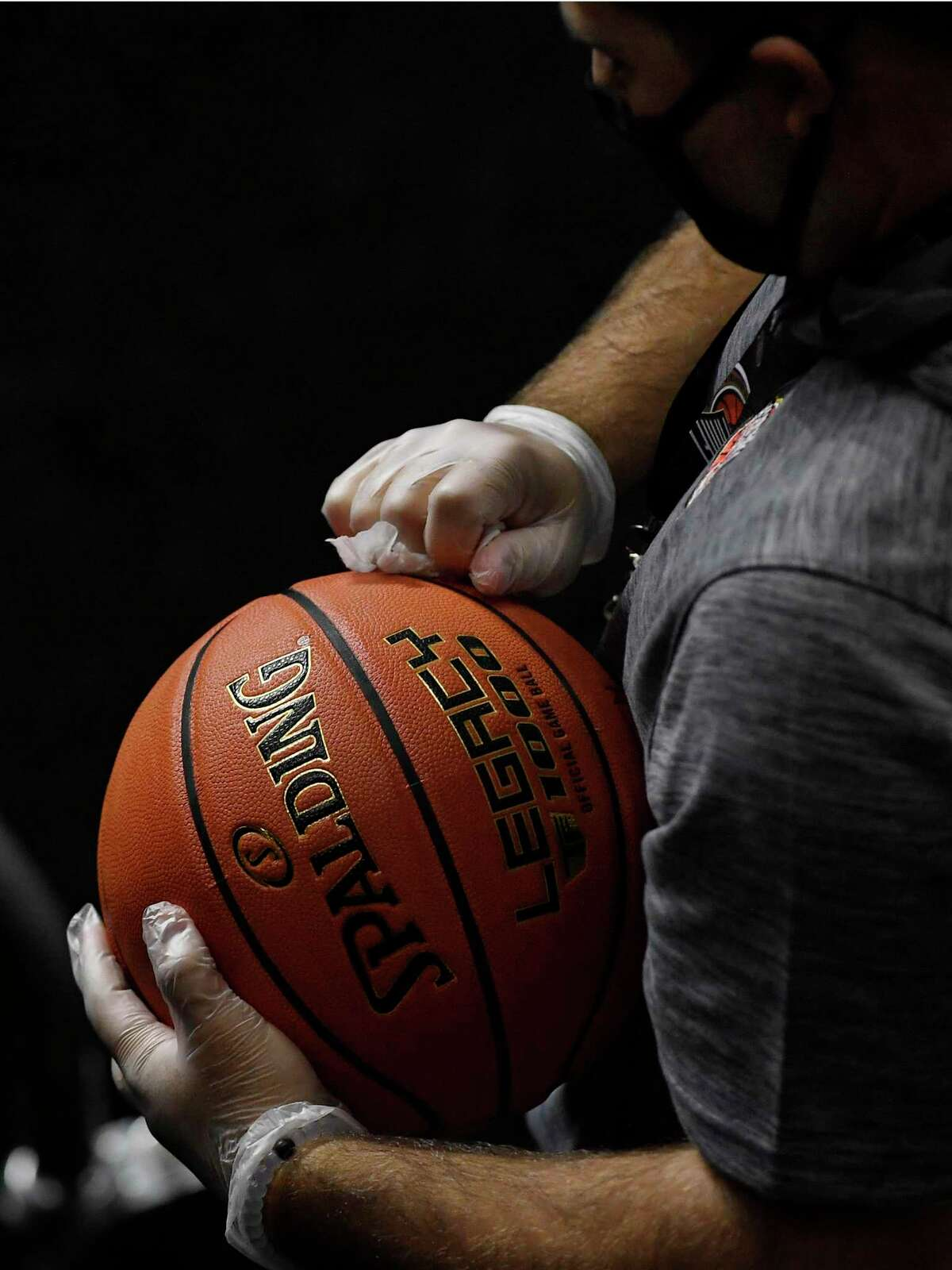 A man cleans basketballs to be used in an upcoming NCAA college basketball game between San Francisco and Virginia with alcohol wipes, Friday, Nov. 27, 2020, in Uncasville.