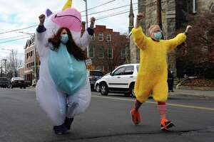 Mayor Mark Boughton, right, dressed as a chicken, and Taylor O'Brien, the city's public relations coordinator, dressed as a unicorn, are competing to raise the most money for Danbury area food banks. The looser was suppose to dress up in a costume and run from city hall to the library but they both decided to make the run. Friday, November 27, 2020, in Danbury, Conn.