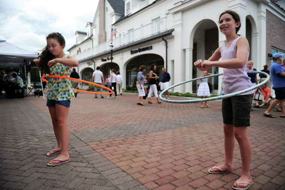 Lulu Murphy, 8, left, and her sister, Delia, 10, show off their hula-hoop skills at Classic 50s Night at the Brick Walk Promenade in Fairfield on Saturday, July 10, 2010. Photo: Lindsay Niegelberg / Connecticut Post