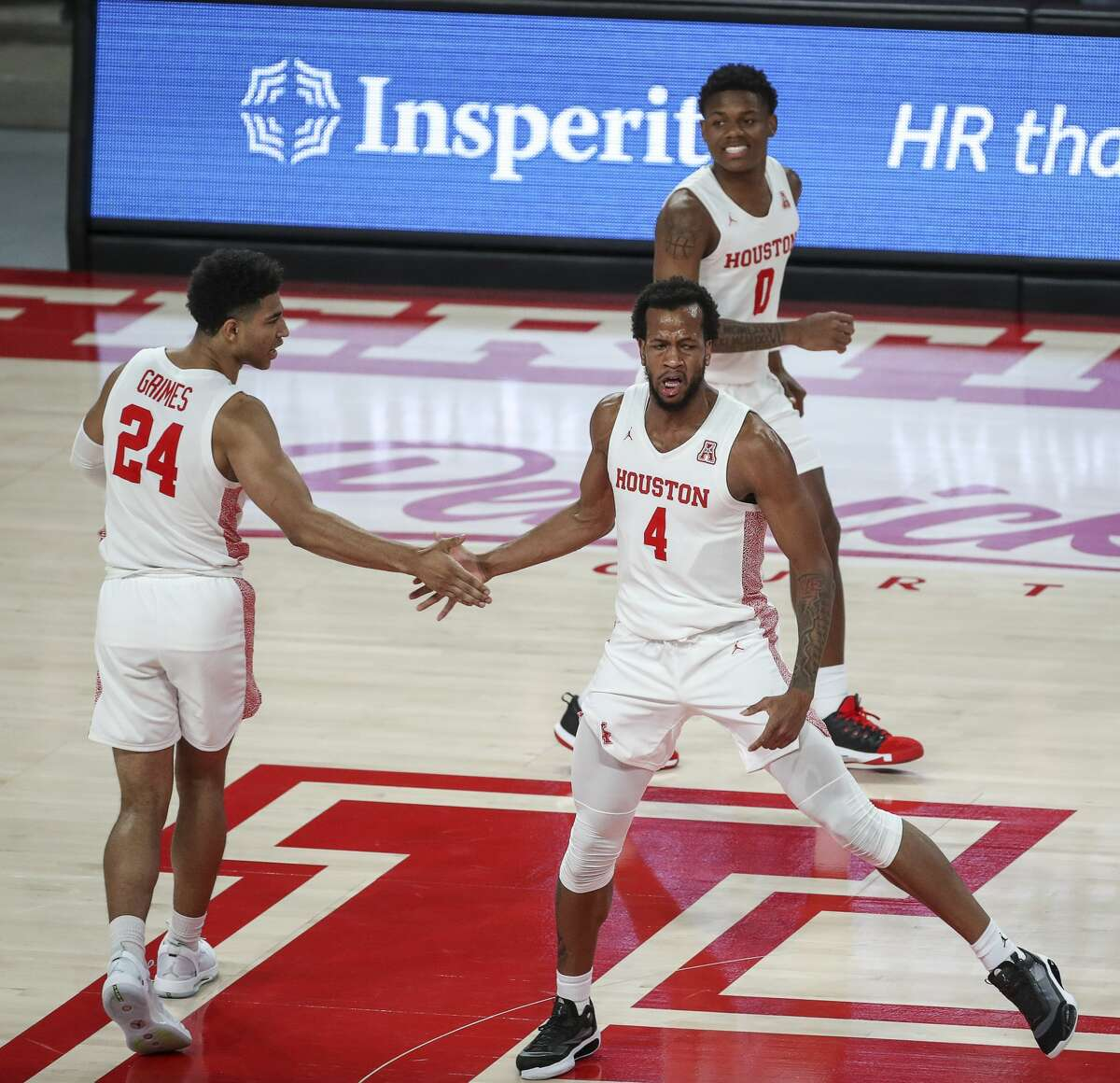 Houston Cougars forward Justin Gorham (4) celebrates with guard Quentin Grimes (24) as guard Marcus Sasser (0) smiles during the first half of an NCAA basketball game Friday, Nov. 27, 2020, at the Fertitta Center in Houston.
