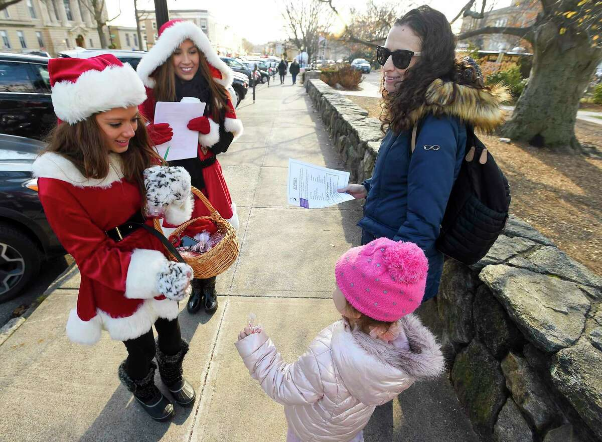 Bianca Lupinacei and Vanessa Hincapie, dressed up in Holiday fashion passing out candy canes and fliers for Sophia's during the 11th Annual Holiday Stroll in Greenwich, Conn. on Dec. 7, 2019.
