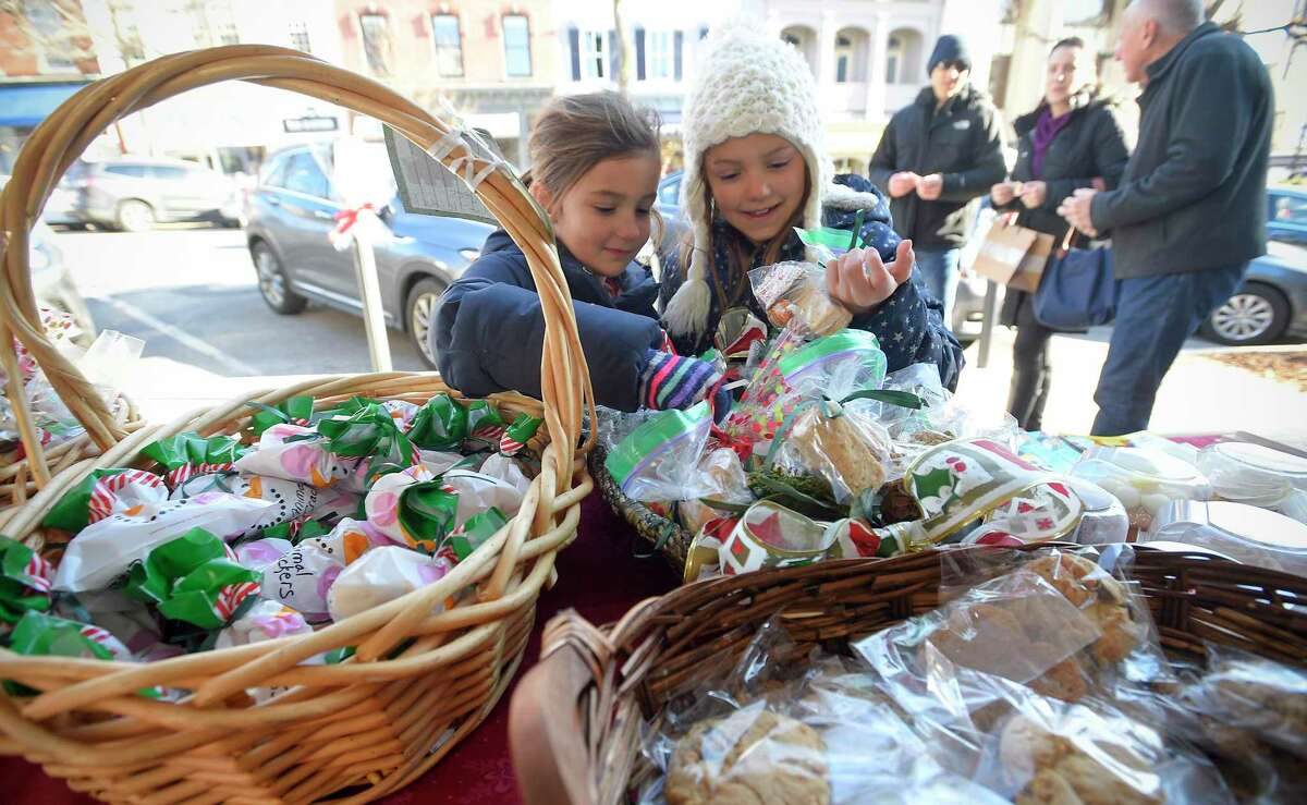 Hazel McCauley, 8, and her sister Violet McCauley, 6, sort through holiday treats they were helping pass out to shoppers passing by the Greenwich Baptist Church