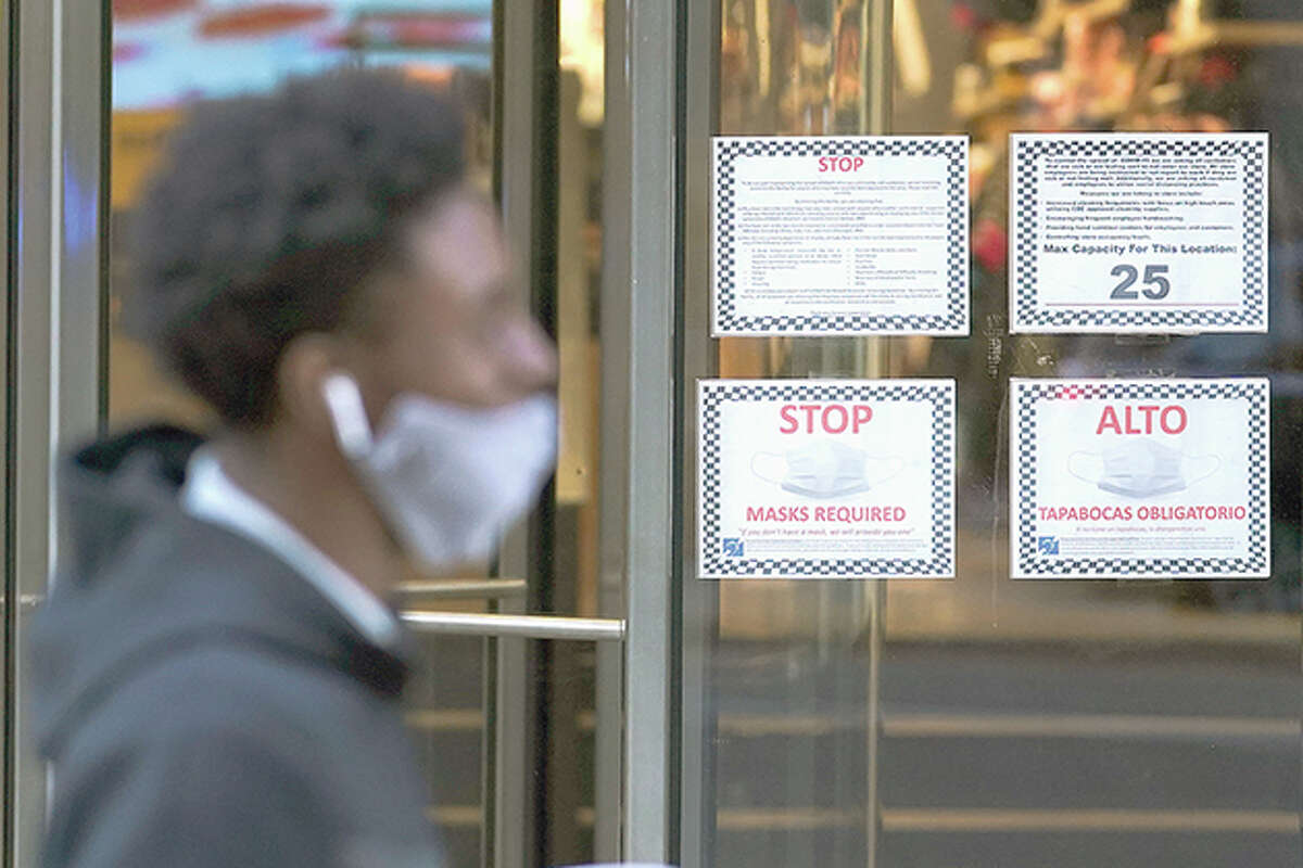 A pedestrian walks past COVID-19 precaution signs outside a retail store. The accelerating surge of coronavirus cases across the U.S. is causing an existential crisis for America's retailers and worrying their customers just as the critically important holiday shopping season begins.