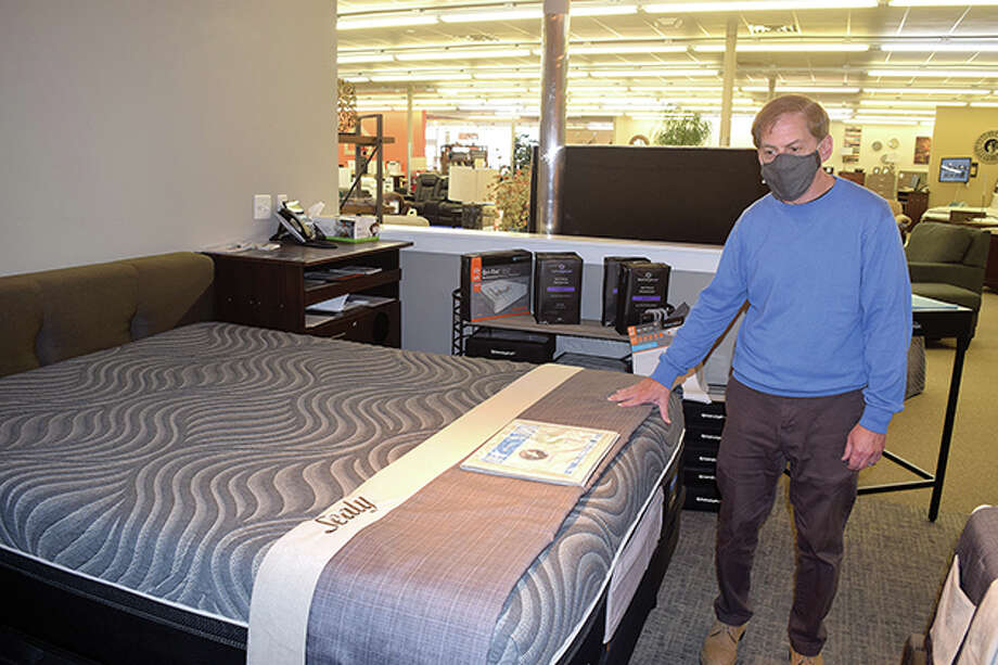 Barry Seidman of Ashley HomeStore in Jacksonville shows off some of the more popular mattresses his store sells. The furniture store has seen moderate increases in mattress and recliner sales, mirroring a national trend, Seidman said. Photo: Marco Cartolano | Journal-Courier
