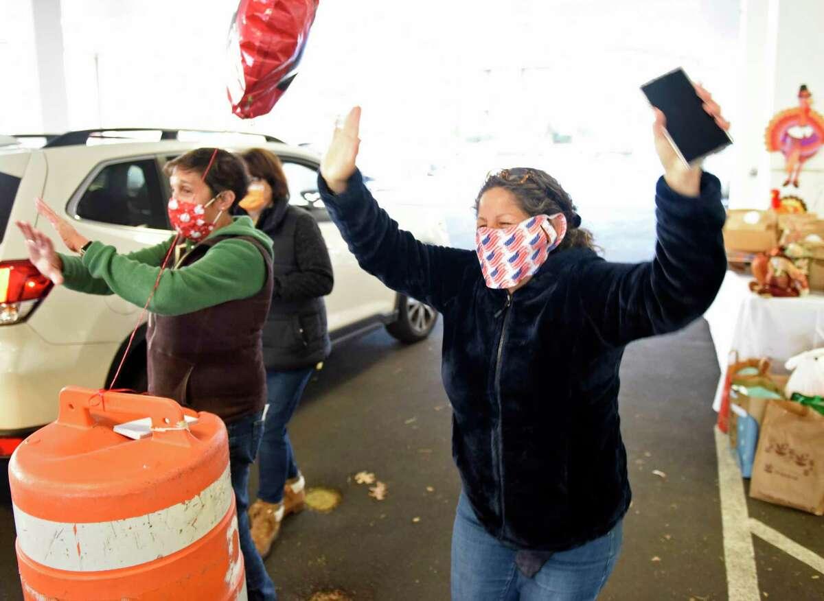 Stamford Senior Center Hispanic Coordinator Lili Winsor dances while handing out Thanksgiving meals to seniors.