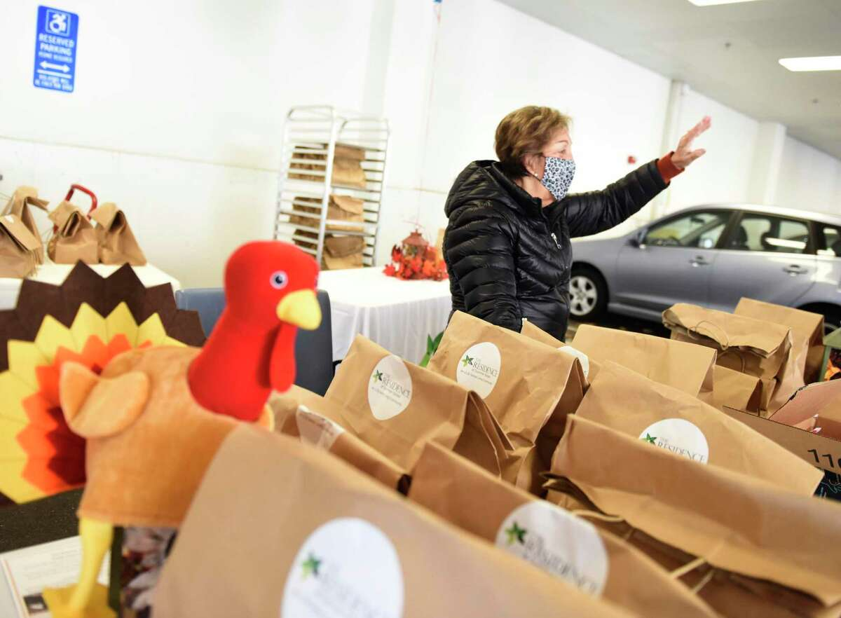 Stamford Senior Center volunteer Pamela Koutroubis waves while handing out Thanksgiving meals to seniors at The Residence at Summer Street senior living facility in Stamford, Conn. Tuesday, Nov. 24, 2020. 150 Thanksgiving meals featuring turkey and sides were distributed to seniors in a socially-distant drive-thru at the senior living center. Additionally, nonperishable food was collected to be donated to Stamford nonprofit Person-to-Person.