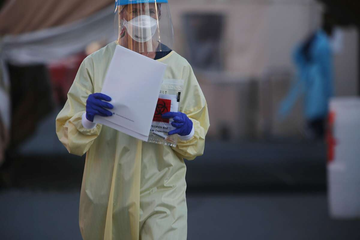 A worker at a coronavirus test site carries paperwork and a test kit in San Francisco. A surge in infections is putting a strain on test sites and contract tracing programs.