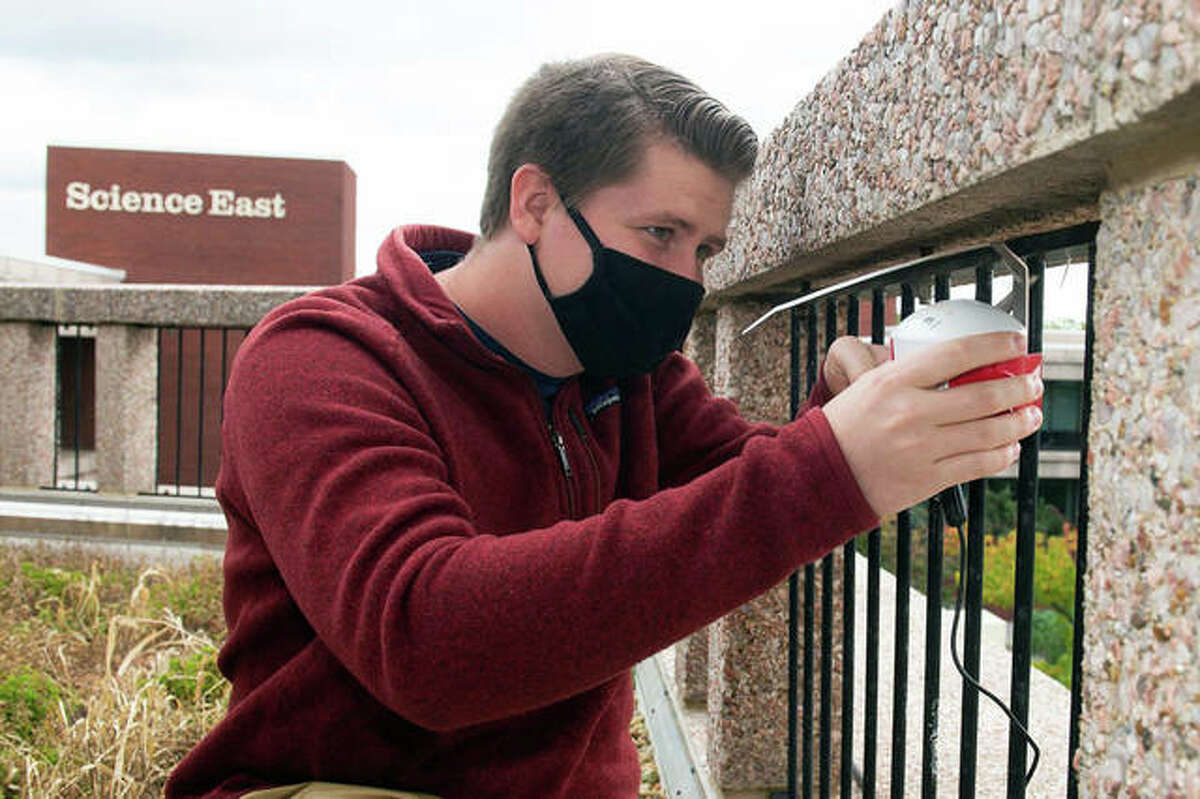 Josh Gifford secures the PurpleAir air quality monitor on SIUE's campus after downloading the data from the monitor.