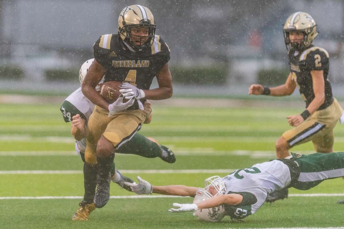 Bulldogs Kerrington Broussard (4) carries the ball in the second quarter, breaking away from several Panthers defenders. The Nederland Bulldogs hosted the Kingwood Park Panthers in a rain-soaked game Friday afternoon. Photo made on November 27, 2020. Fran Ruchalski/The Enterprise
