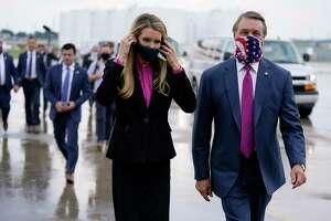 FILE- In this July 15, 2020, file photo Sen. Kelly Loeffler, R-Ga., puts on a face mask as she walks with Sen. David Perdue, R-Ga., right, at UPS Hapeville Airport Hub in Atlanta. (AP Photo/Evan Vucci, File)
