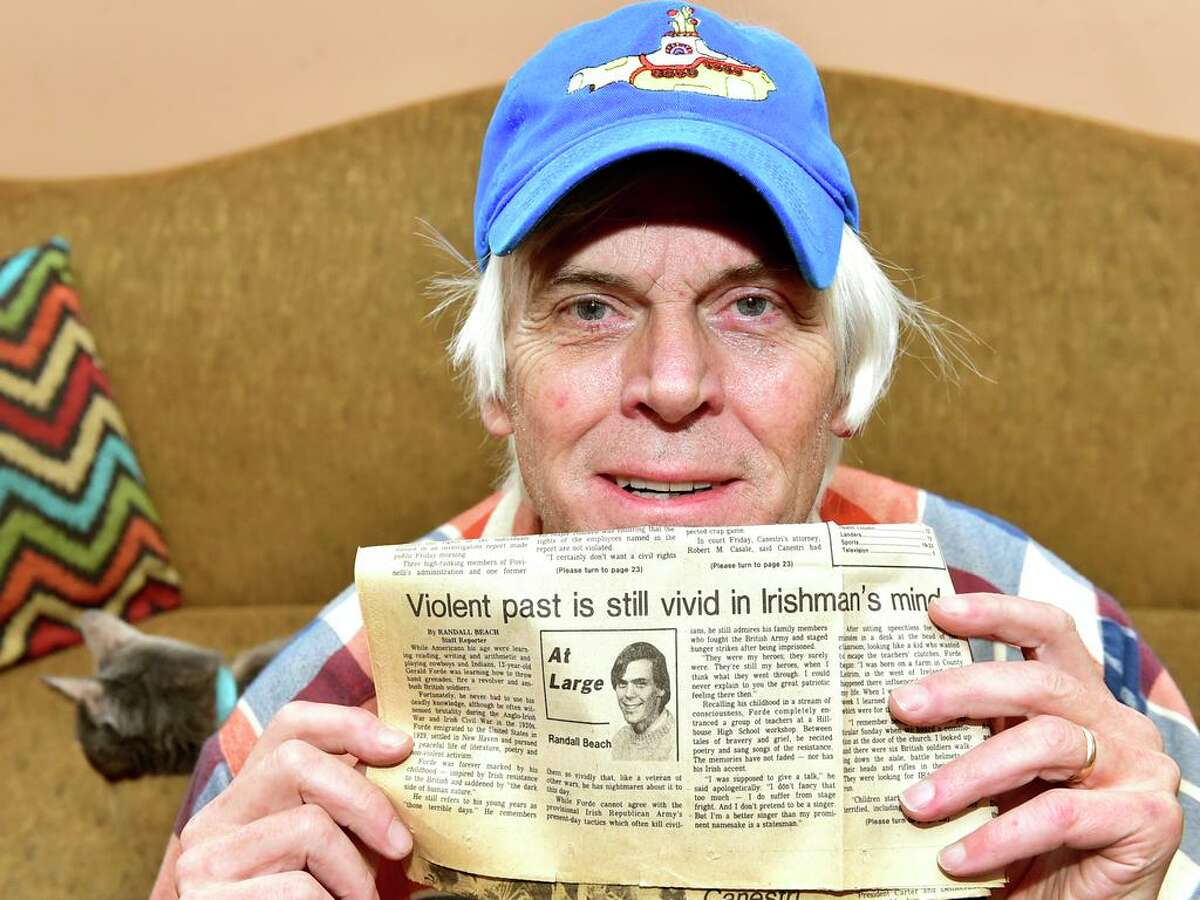 Long-time New Haven Register columnist and reporter Randall Beach, who has just retired from the newspaper after a total of 32 years on the job after two-separate stints, holds his very first Register column written in November 1980 while relaxing in his New Haven home.