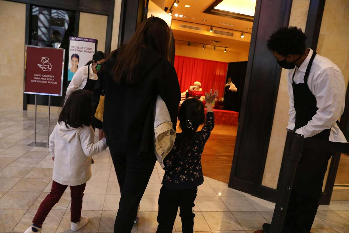 Stephanie Lagleva holds the hands of daughter Marcella Lagleva (right), 4, as she waves to Santa, and friend Aviana Chen, 4, as they peek in the mall store to say hello to Santa at Stonestown Galleria.