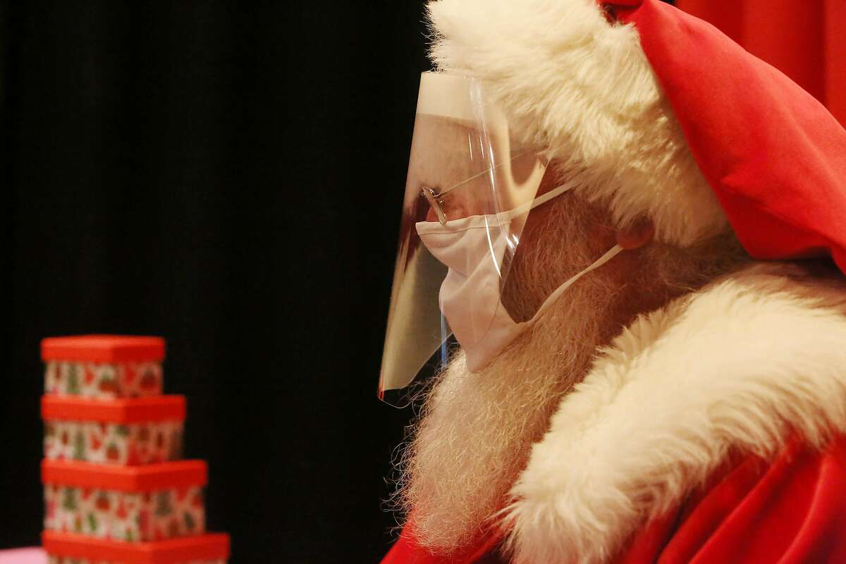 The Stonestown Galleria Santa wears a mask and face shield.