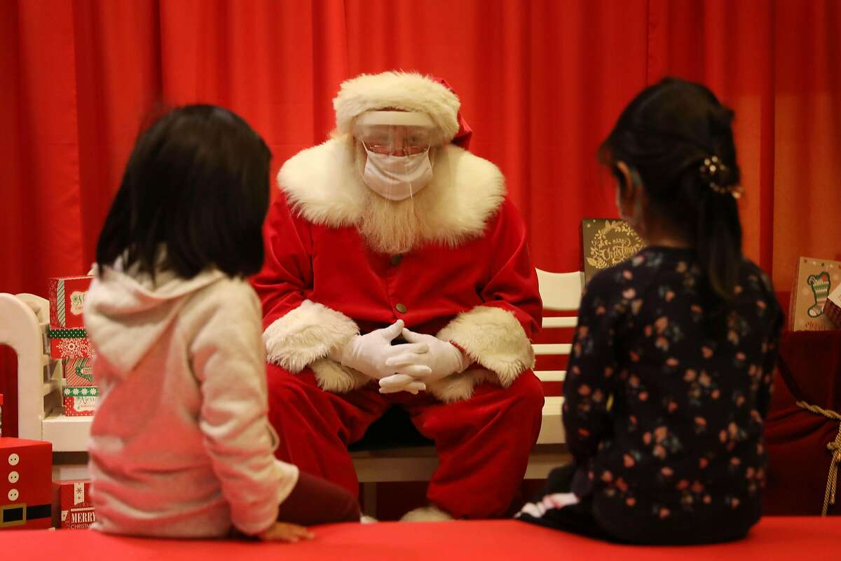 Aviana Chen (left) and Marcella Lagleva keep their distance as they visit Santa at a Stonestown Galleria store.