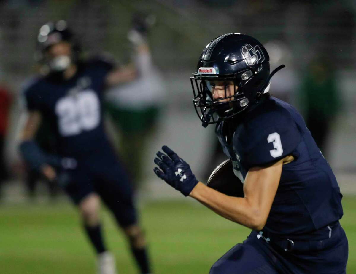 College Park defensive back Joseph Golden (3) returns the ball after intercepting a pass from The Woodlands quarterback Connor Dechiro during the first quarter of a high school District 13-6A high school football game in Shenandoah.