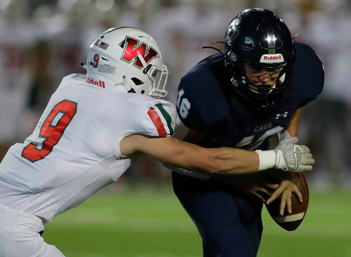 College Park wide receiver Alex Brigman (16) has the ball stripped by The Woodlands linebacker Noah Polotko (9) during the first quarter of a high school District 13-6A high school football game in Shenandoah. The Woodlands defensive linemen Bradley Warren recovered the fumble for the Highlanders.