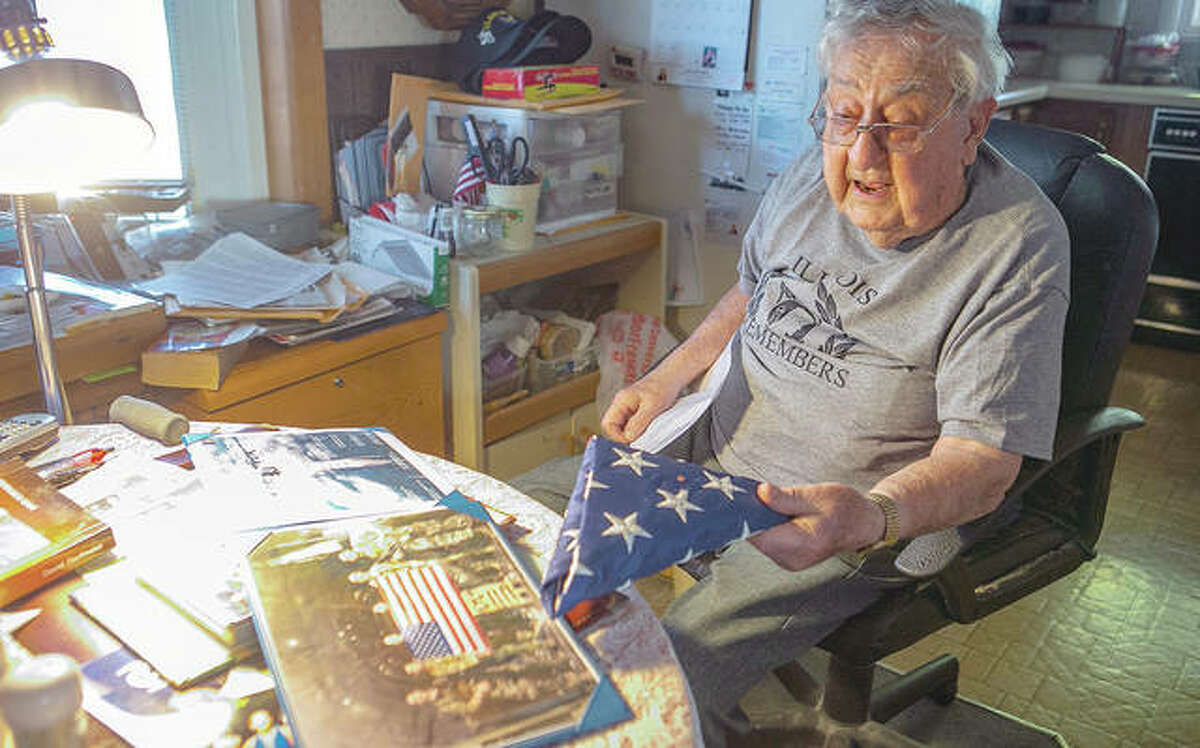 Robert Teichgraeber, 100, talks about the many gifts and honors he has received for his service in World War II. He holds a flag flown in his honor in combat over Afghanistan. He survived 421 days as a prisoner after his plane was shot down during a bombing run in World War II.