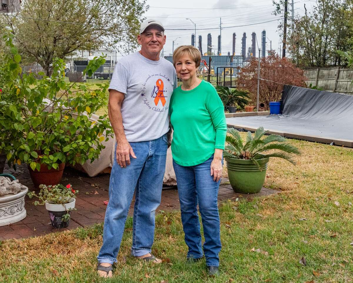 Gary and Susan Miguez stand in the backyard of their home with the towers of the TPC Plant seen over their left shoulders. The plant is about a quarter of a mile from their home and the explosion caused a great deal of structural damage to their home. Port Neches residents are still living with the results of the TPC Group plant explosion one year later. Friday, Nov. 27, marked one year since Port Neches and other surrounding towns in Southeast Texas awoke with a thunderous boom and an orange, glowing sky above their neighborhoods as a chemical plant erupted in flames that burned for the next month. Photo made on November 27, 2020. Fran Ruchalski/The Enterprise