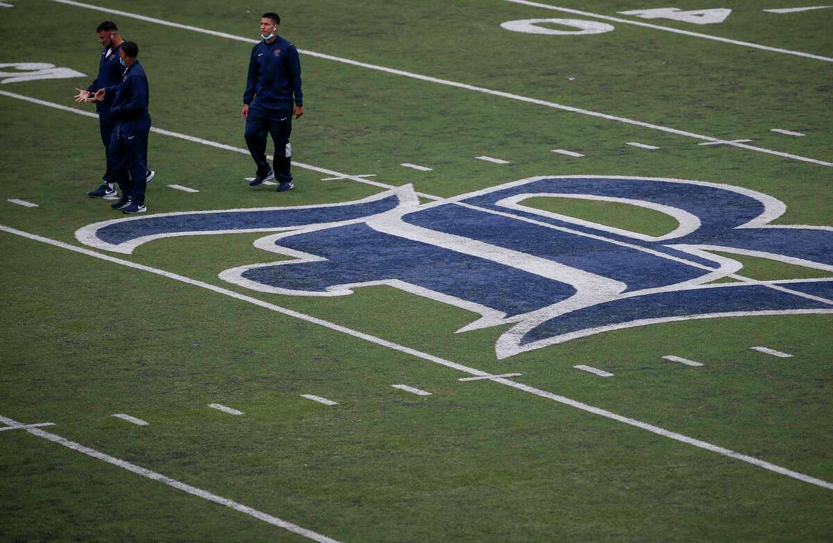 People walk on the field before an NCAA football game Saturday, Nov. 28, 2020, at Rice Stadium in Houston. The game has been delayed for additional testing.