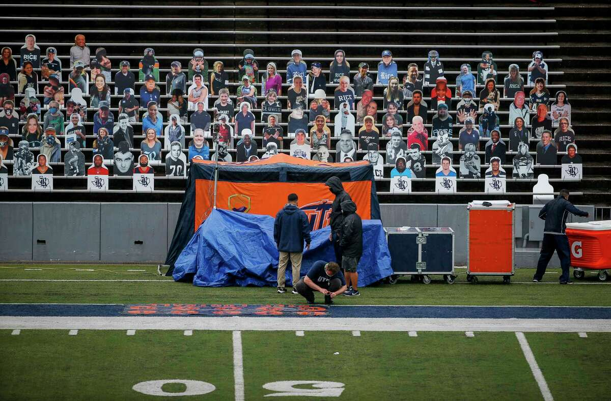 People work on the sidelines before an NCAA football game Saturday, Nov. 28, 2020, at Rice Stadium in Houston. The game has been delayed for additional testing.