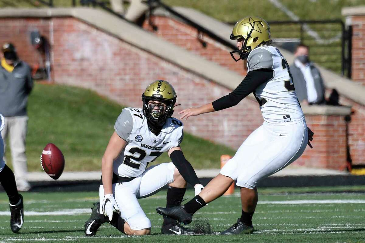 Vanderbilt's Sarah Fuller, right, kicks off as Ryan McCord (27) holds to start the second half of an NCAA college football game against Missouri Saturday, Nov. 28, 2020, in Columbia, Mo. With the kick, Fuller became the first female to play in a Southeastern Conference football game.