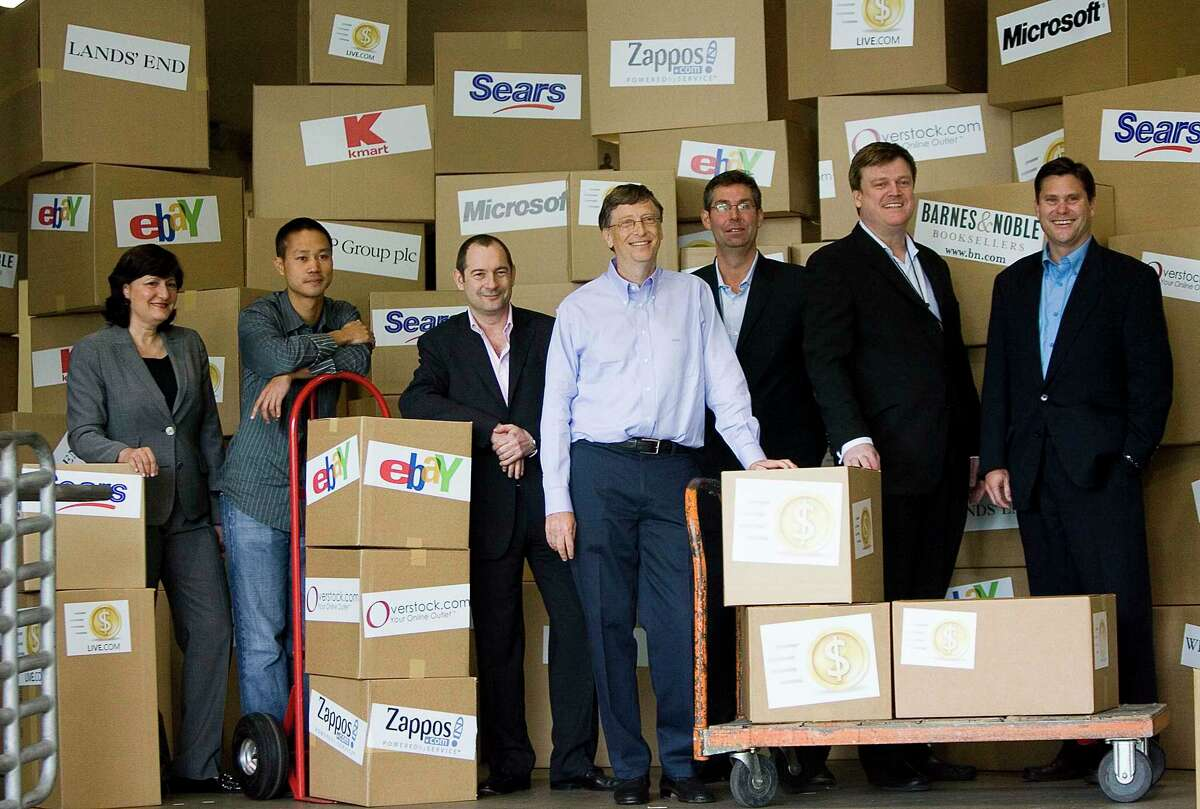 In this May 21, 2008, file photo, Marie J. Toulantis, CEO of Barnes & Noble.com; Tony Hsieh, CEO of Zappos.com; Rob Norman, CEO of GroupM Interaction Worldwide; Bill Gates, Chairman of Microsoft Corp.; Matt Ackley, VP of Internet Marketing and Advertising, eBay Inc.; Patrick Byrne, CEO of Overstock.com; and Jim Barr, President, Online, Sears Holdings, pose for a photo after announcing Live Search Cashback programs, at Microsoft headquarters in Redmond, Wash. Hsieh, retired CEO of Las Vegas-based online shoe retailer Zappos.com, has died. Hsieh was with family when he died Friday, Nov. 27, 2020, according to a statement from DTP Companies, which he founded.
