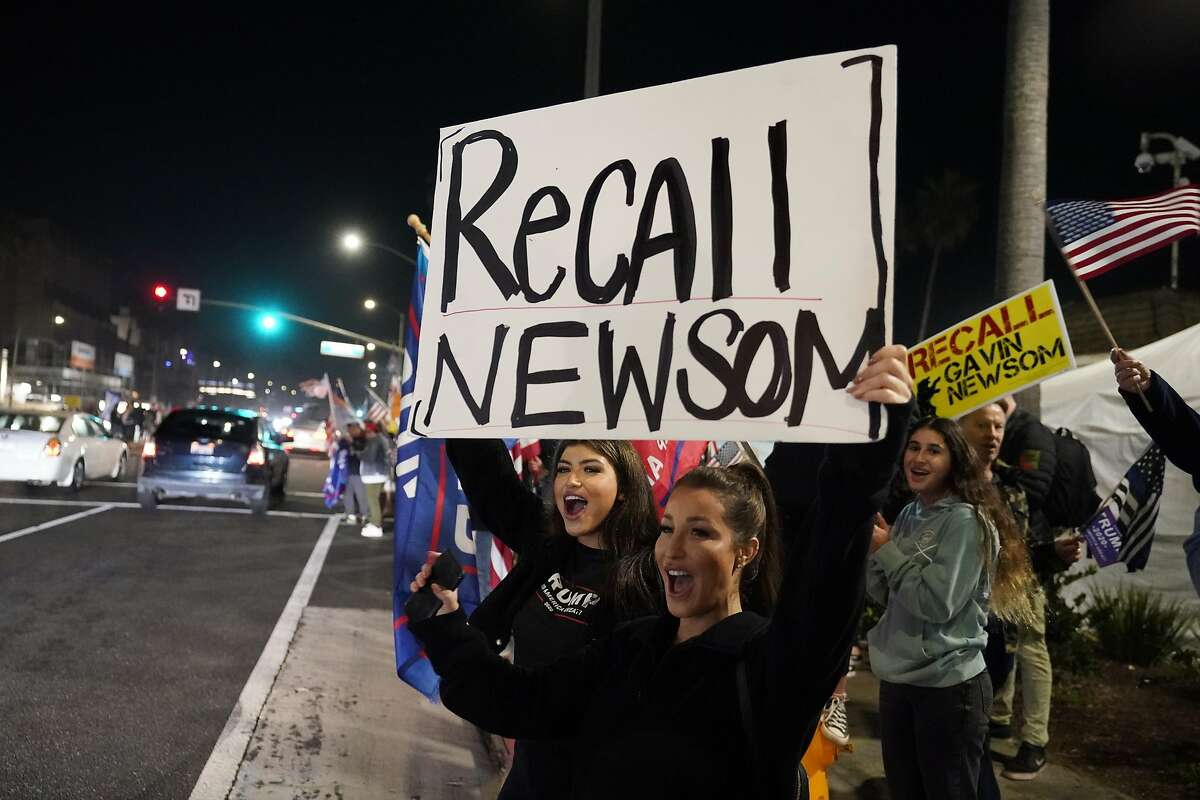 Demonstrators shout slogans while carrying a sign calling for a recall on Gov. Gavin Newsom Saturday, Nov. 21, 2020 during a protest against a stay-at-home order amid the COVID-19 pandemic in Huntington Beach, Calif.