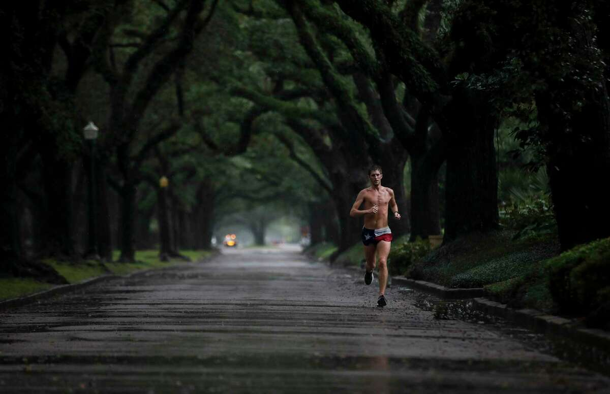 Andrew Littlefield runs in the rain Saturday, Nov. 28, 2020, along South Boulevard in Houston. He called running