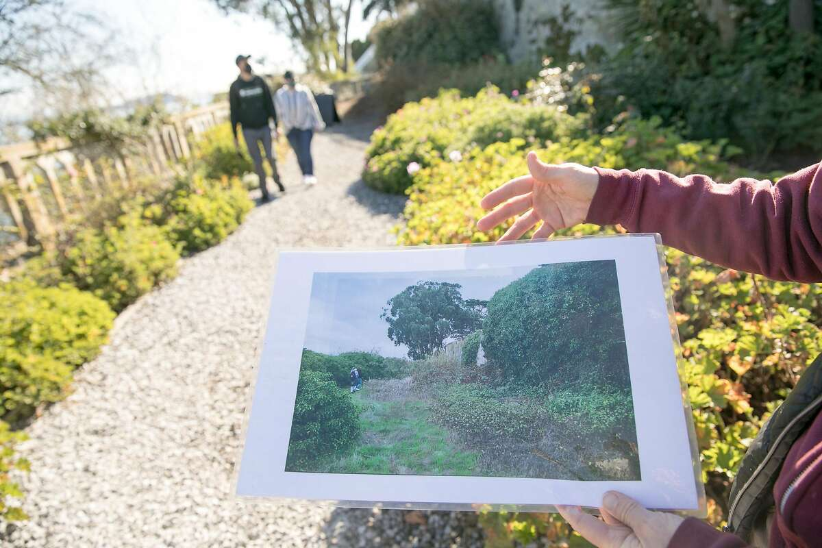 Gardener Shelagh Fritz displays a photograph to show the condition of the Rose Garden before they started rehabilitating it on Alcatraz Island in San Francisco on Nov. 23, 2020. For the past 17 years, the National Park Service and Golden Gate National Parks Conservancy have been uncovering and rehabilitating many gardens on the island that were created and maintained during its time as a military base and later a prison.