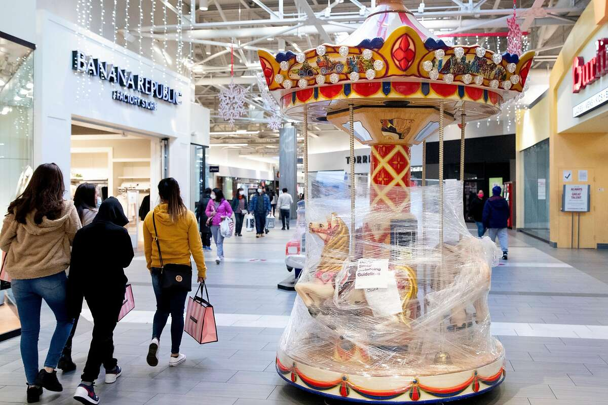 Visitors walk past a carousel encased in plastic at the Great Mall in Milpitas on Friday. Santa Clara County has tightened rules.