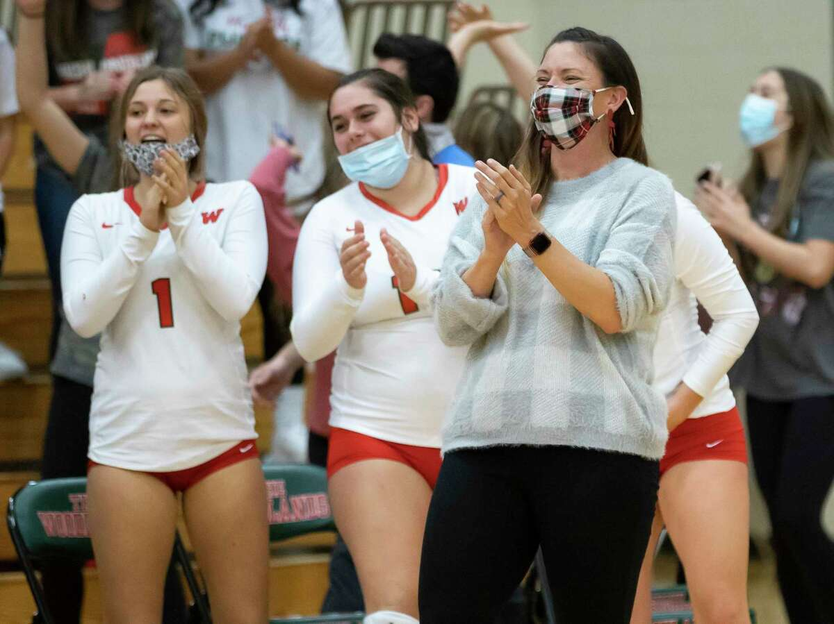 The Woodlands head coach Terri Wade and her team celebrate after scoring a point during the fifth set of a Region II-6A quarterfinal volleyball playoff game against Klein Cain at The Woodlands High School, Saturday, Nov. 28, 2020, in The Woodlands.