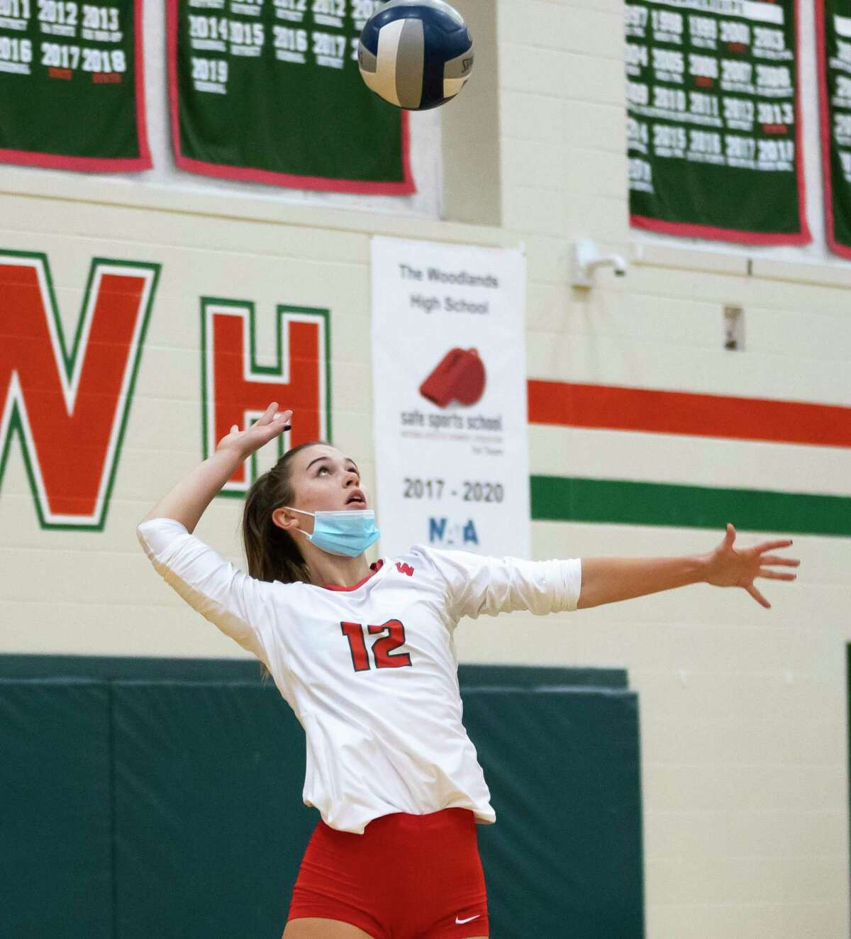The Woodlands setter Clara Brower (12) serves the ball during the first set of a Region II-6A quarterfinal volleyball playoff game against Klein Cain at The Woodlands High School, Saturday, Nov. 28, 2020, in The Woodlands.