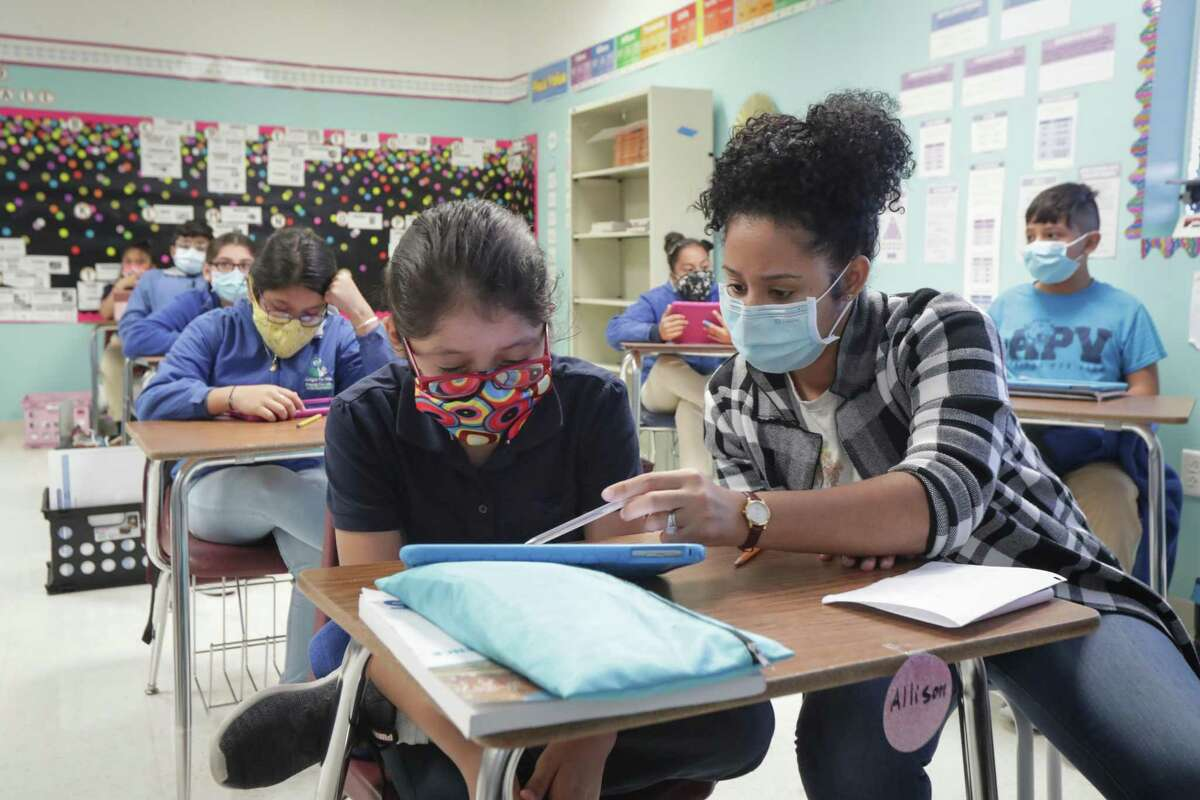 Teacher's aide Calderon Dayana works with fifth grader Allison Rivera earlier this month at the Gulfton-area Amigos Por Vida - Friends For Life Public Charter School, which appears among the top scorers in this year's Children at Risk school rankings.