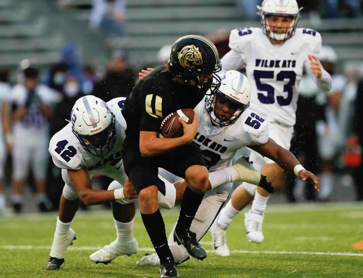 Willis defensive lineman David Soriano (42) and Eli'jah Hubbard (52) tackle Conroe quarterback Clayton Garlock (9) for a loss during the second quarter of a District 13-6A high school football game at Buddy Moorhead Stadium, Saturday, Nov. 28, 2020, in Conroe.