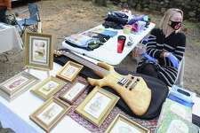 """Carolyn Hill-Bjerke of Weston at a table featuring some of Wayne """"Braino"""" Bjerke, her husband's artwork at the Norfield Grange's Black Friday Trunk Sale on Nov. 27, 2020, in Weston, Conn."""