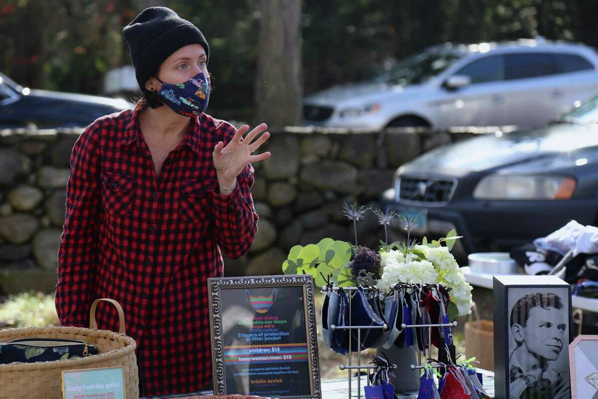 Kristin Zovich of Weston sells her handmade masks and other products at the Norfield Grange's Black Friday Trunk Sale on Nov. 27, 2020, in Weston, Conn. Lynn Kimberly, an officer with the grange, came up with what she described as a