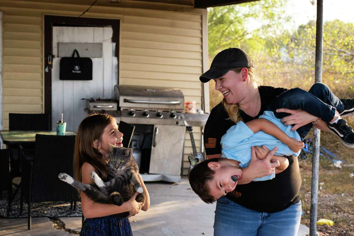 Alicia Caballero, 28, plays with her kids Jameson, 4, and Kylie Caballero, 7, at their family home in Kingsville, Texas. On Monday November 23, 2020.