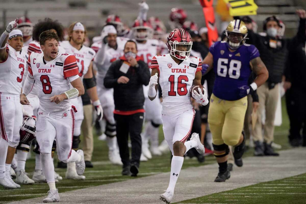 Utah safety Zemaiah Vaughn (16) runs 73 yards as quarterback Jake Bentley (8) runs next to him on the sideline after Vaughn intercepted a Washington pass during the first half of an NCAA college football game Saturday, Nov. 28, 2020, in Seattle.
