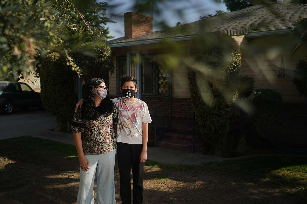 Patricio Gonzalez, 12, who has asthma, with his mother, Gilda Zarate-Gonzalez, outside their home in Fresno, Calif., where smoke from the Creek Fire in Sierra National Forest has been problem for air quality, on Oct. 22, 2020. Fires are making California's air more dangerous. How much that hurts depends largely on where you live and how much money your family has. (Chang W. Lee/The New York Times)