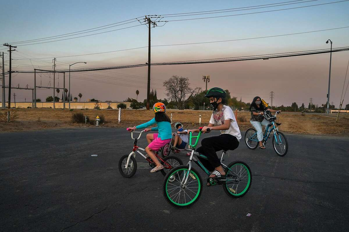Patricio Gonzalez, 12, center right, and his family ride bikes near their home in Fresno, Calif., where smoke from the Creek Fire in the Sierra National Forest has been problem for air quality, on Oct. 22, 2020. Fires are making California's air more dangerous. How much that hurts depends largely on where you live and how much money your family has. (Chang W. Lee/The New York Times)