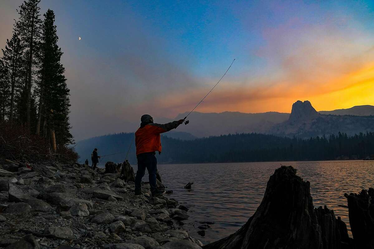 Joshua Moreno fishes as smoke from the Creek Fire looms over the Sierra National Forest in California, on Oct. 23, 2020. Fires are making California's air more dangerous. How much that hurts depends largely on where you live and how much money your family has. (Chang W. Lee/The New York Times)