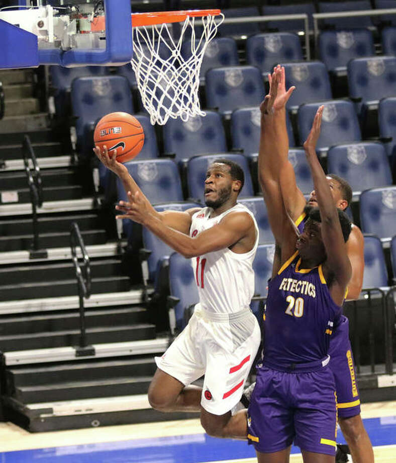 SIUE's Courtney Carter (left) goes to the rim for a layup after driving past UHSP's Alassane Ba (20) on Saturday night at Chaifetz Center in St. Louis. Photo: Greg Shashack / Hearst Illinois