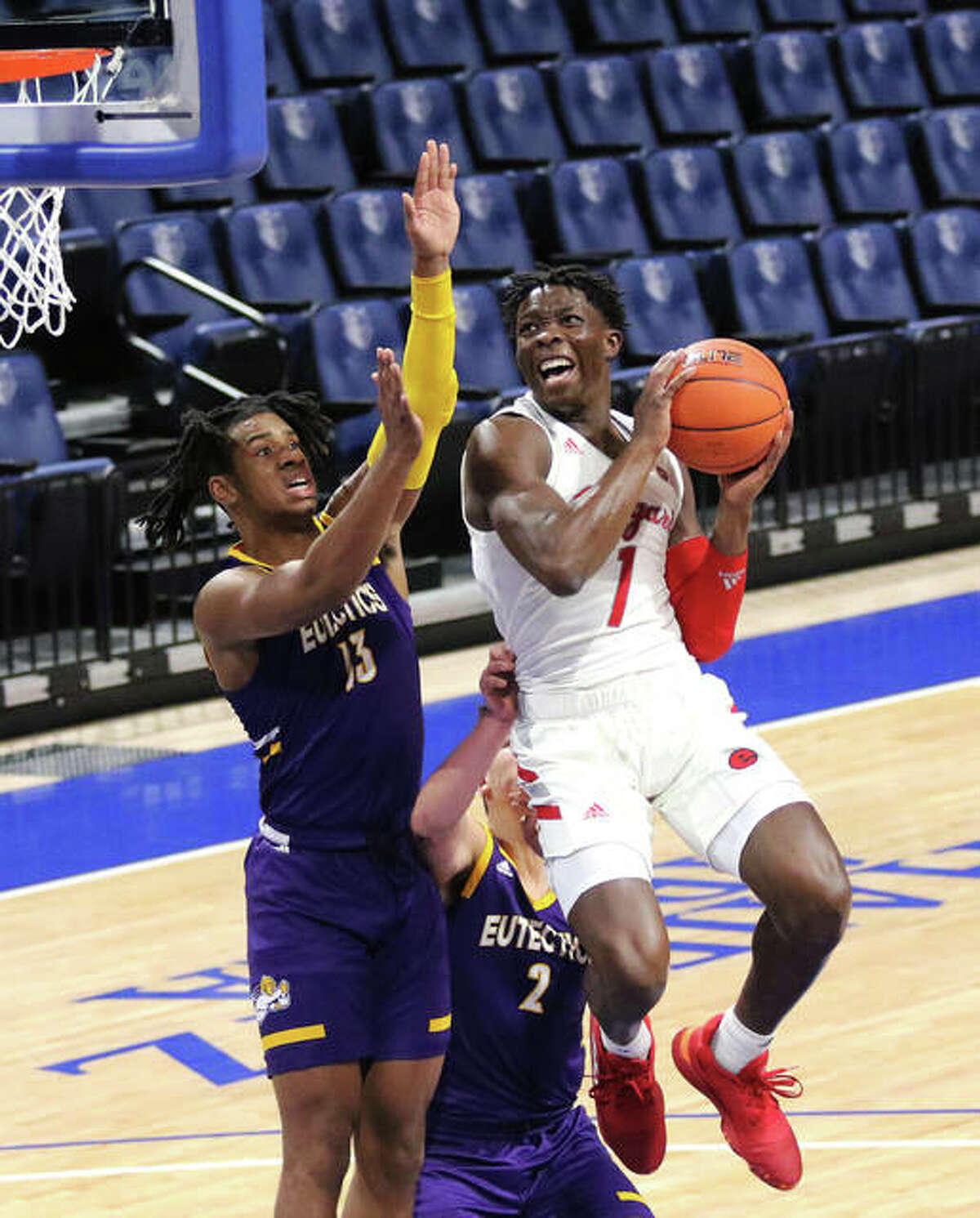 SIUE's Mike Adewunmi (1) scores while driving to the basket against UHSP's Jason Udolisa (left) and Devon Howard on Saturday night at Chaifetz Center in St. Louis.