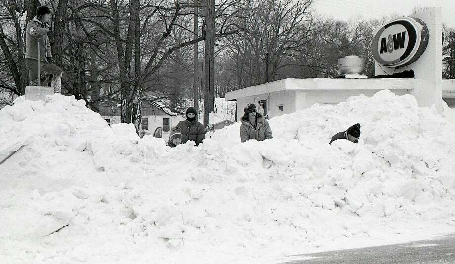 """Shoveling snow at the former A & W after the blizzard of January 1978. According to National Weather Service records, """"The incredible blizzard of January 26-27, 1978 evolved out of a winter that was infamous for cold and storms. The winter of 1977-78 thus far had been one the coldest, since records began, in many areas from the Rockies eastward to the Appalachians."""" (Manistee County Historical Museum photo)"""