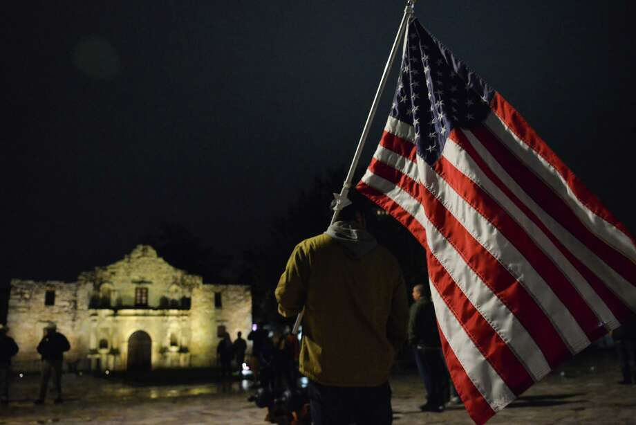 "A man holding the American flag stands in front of the Alamo Saturday night prior to a ""social Gathering"" to protest the San Antonio curfew. Photo: Robin Jerstad, San Antonio Express-News / **MANDATORY CREDIT FOR PHOTOG AND SAN ANTONIO EXPRESS-NEWS/NO SALES/MAGS OUT?TV"