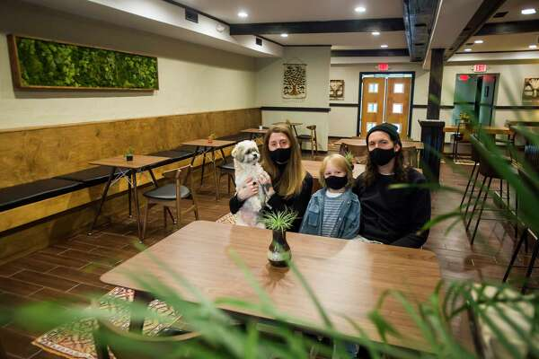 Lisa Kuznicki, left, Evan Sumrell, right, and their son Stanley, center, pose for a portrait inside Aster, the family's new farm-to-table restaurant located at 134 Ashman St. in downtown Midland. (Katy Kildee/kkildee@mdn.net)