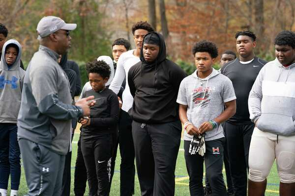 """Terrence Byrd, coach of the Maryland Heat Youth Football team, talks to his players at the beginning of practice on a field behind Carl Sandburg Middle School in Alexandria, Va., on Nov. 21. Because of the coronavirus, the team had to """"field shop"""" and has played games in Delaware and Pennsylvania."""