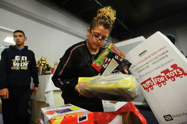 Seana Nieves, of Derby, sorts toys for Greater Bridgeport Christian Fellowship's Toys for Tots drive at 180 Boston Avenue in Bridgeport, Conn. on Sunday, December 9, 2018.